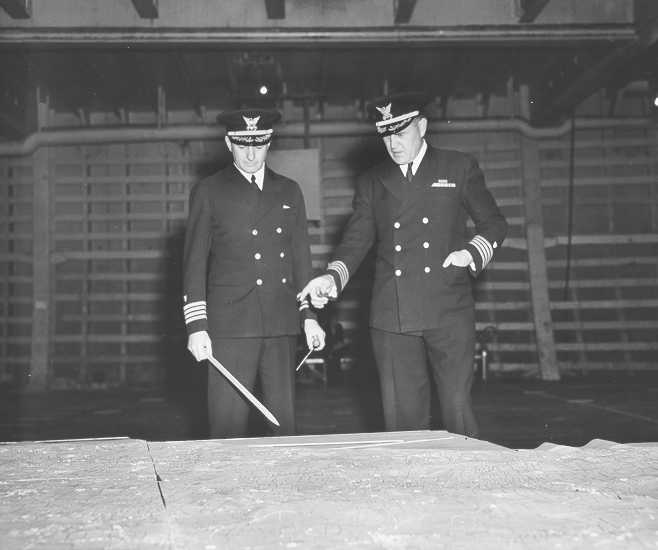 UNSUNG HEROES: Coast Guard Captains Edward Fritzche (left) and Miles Imlay (right) discuss the invasion of Omaha Beach on a relief map laid out in the hold of the Samuel Chase.