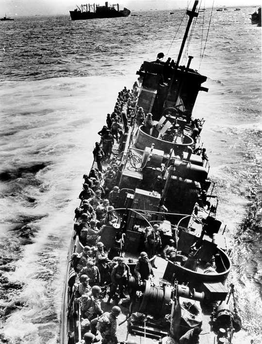 "The Coast Guard LCI(L)-85, battered by enemy fire after approaching Omaha Beach, prepares to evacuate the troops she was transporting to an awaiting transport.  The ""85"" sank shortly after this photograph was taken.  The LCI(L)-85 was one of four Coast Guard LCI's that were destroyed on D-Day."